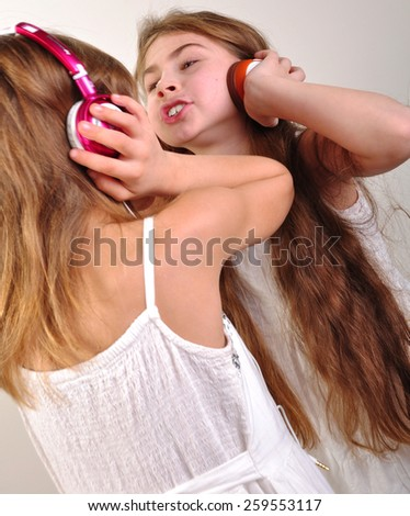 portrait of two happy children listening to music - stock photo