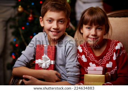 Portrait of two happy children with Christmas gifts looking at camera - stock photo