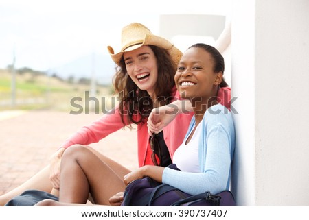 Portrait of two happy female friends sitting at railway station  - stock photo