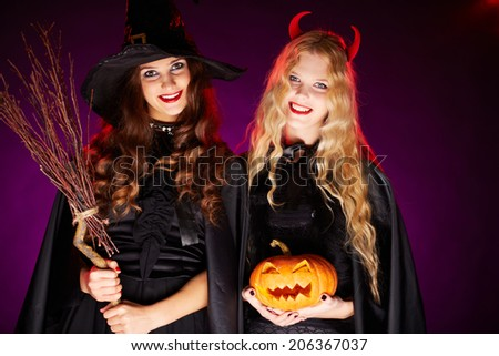 Portrait of two happy females with broom and pumpkin looking at camera with smiles - stock photo