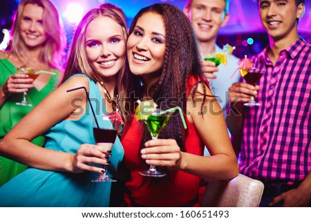 Portrait of two happy girlfriends with cocktails looking at camera at party - stock photo