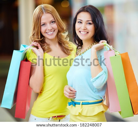 Portrait of two happy girls in smart casual holding paperbags - stock photo