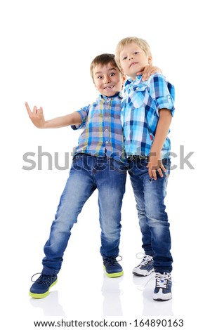 Portrait of two happy little fashion boys in checked shirts and blue jeans isolated on a white background - stock photo