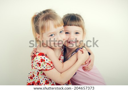 Portrait of two happy little sisters - stock photo