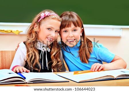 Portrait of two happy schoolgirls in a classroom. - stock photo