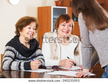 Portrait of two happy senior women with papers and agency employee - stock photo