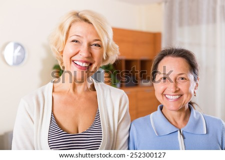 Portrait of two happy smiling  female pensioners at home. Focus on blonde - stock photo