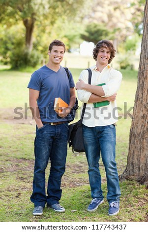 Portrait of two happy standing male students in a park - stock photo