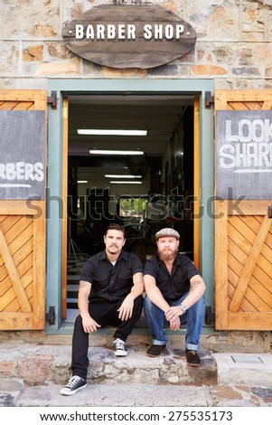 Portrait Of Two Hipster Barbers Standing Outside Shop - stock photo