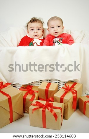 portrait of two infant baby boys seating in an enormous White laundry basket looking up at the camera wearing red Christmas costume isolated on White background - stock photo