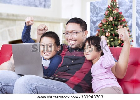 Portrait of two joyful children and their father, playing game on laptop and raise hands together - stock photo