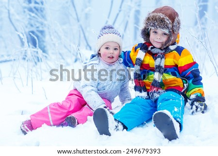 portrait of two kids: boy and girl in winter hat in snow forest at snowflakes background. outdoors winter leisure and lifestyle with children. - stock photo