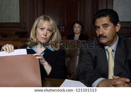 Portrait of two lawyer sitting with woman in the background - stock photo