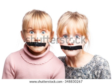 Portrait of two little girls with duct tape on their mouths - silenced child concept - stock photo