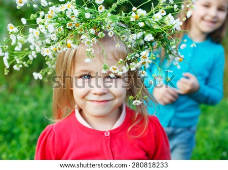Portrait of two little sisters outdoors wearing wreath from white daisies in summer day. Focus on flowers - stock photo