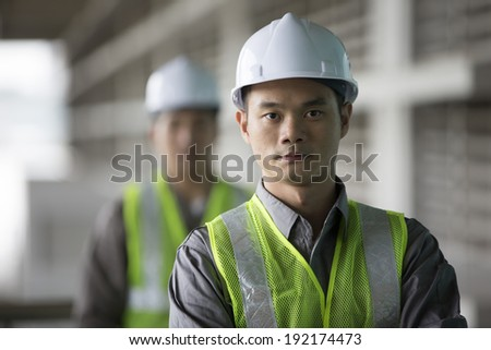 Portrait of two male Chinese industrial engineer's at work - stock photo