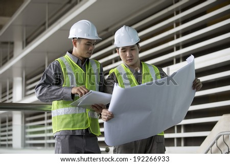 Portrait of two male Chinese industrial engineer's looking at techincal drawing plans. - stock photo