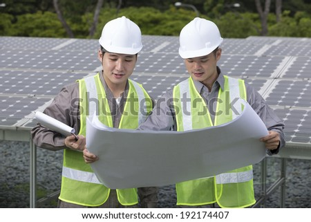 Portrait of two male Chinese solar-panel engineer's looking at techincal drawing plans. - stock photo