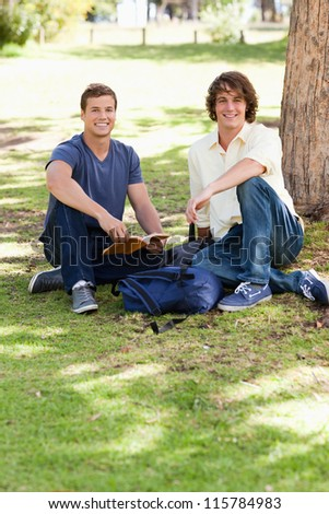 Portrait of two male students studying in a park - stock photo