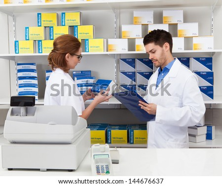 Portrait Of Two Pharmacist Chemist Working In Pharmacy - stock photo
