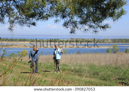 portrait of two photographers working on the river on a sunny day in spring - stock photo