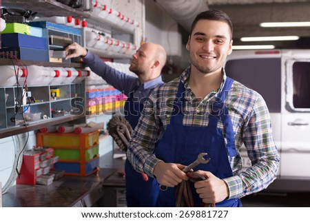 Portrait of two positive adult garage colleagues near facilities - stock photo