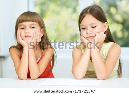 Portrait of two sad little girls are sitting at table - stock photo