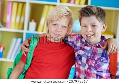Portrait of two school friends with backpacks looking at camera - stock photo