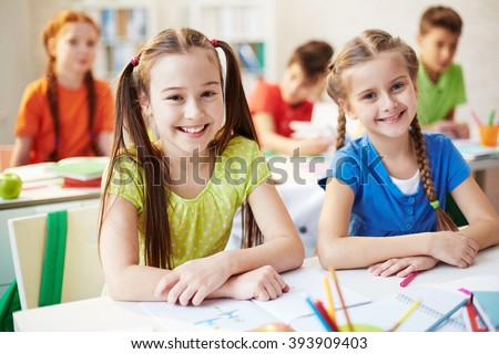 Portrait of two schoolchildren sitting at the desk and smiling at camera - stock photo