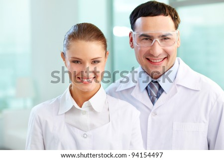 Portrait of two scientists en face looking at camera and smiling - stock photo