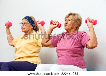 Portrait of two Senior female fitness girls exercising muscles with weights in gym. - stock photo