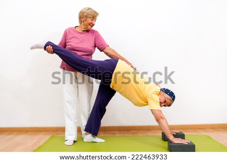Portrait of two Senior ladies helping each other with stretching exercise in gym. - stock photo