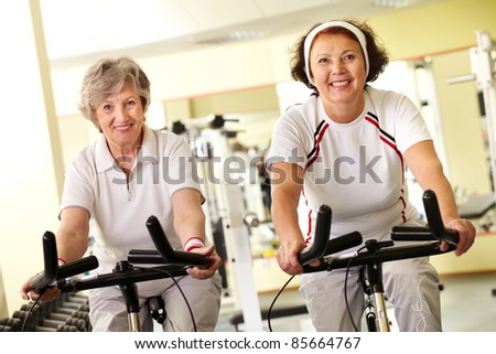 Portrait of two senior women on simulators looking at camera and smiling - stock photo