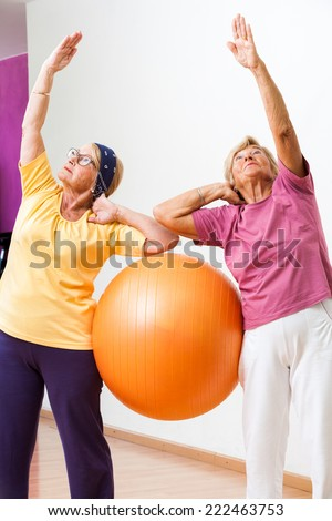 Portrait of Two Senior women stretching with gym ball in health club. - stock photo