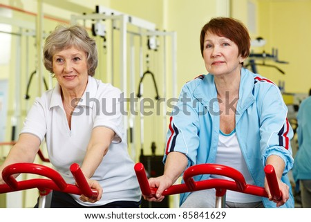 Portrait of two senior women training on exercise bicycle - stock photo
