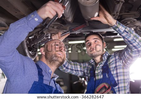 Portrait of two serious professional car mechanics at garage - stock photo