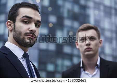 Portrait of two serious young businessmen looking at the camera - stock photo