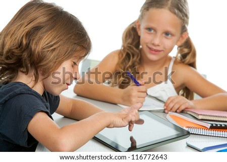 Portrait of two small kids doing homework on digital tablet.Isolated - stock photo