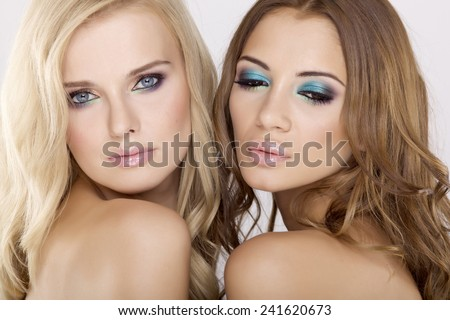 Portrait of two smiling attractive young adult girl friends - blond and brunette cosmetic sensuality and sexy pretty woman on white background - stock photo