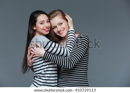 Portrait of two smiling attractive young women standing and hugging over grey background - stock photo