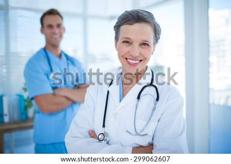 Portrait of two smiling colleagues doctors with arms crossed - stock photo