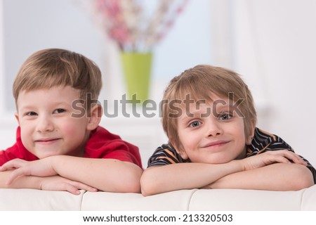 Portrait of two smiling cute boys. two friends leaning on sofa edge - stock photo