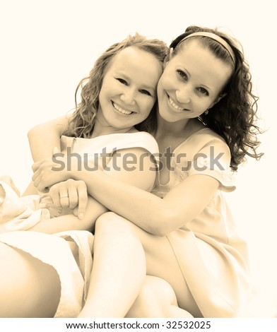 Portrait of two smiling girls on white background - stock photo