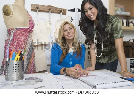 Portrait of two smiling multiethnic female fashion designers at desk - stock photo