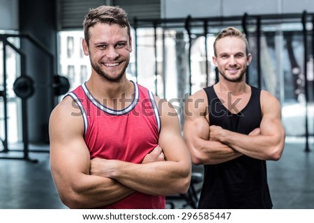 Portrait of two smiling muscular men with arms crossed - stock photo