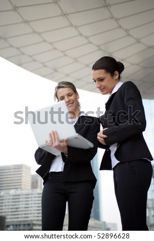 Portrait of two smiling women with a laptop computer - stock photo