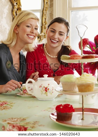 Portrait of two smiling young women sitting at dining table - stock photo