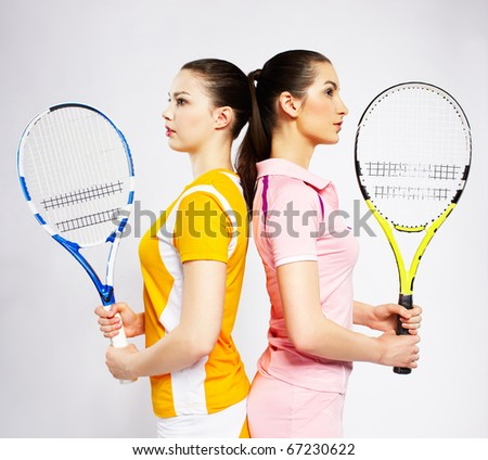 portrait of two sporty girls tennis players with rackets standing back to back - stock photo