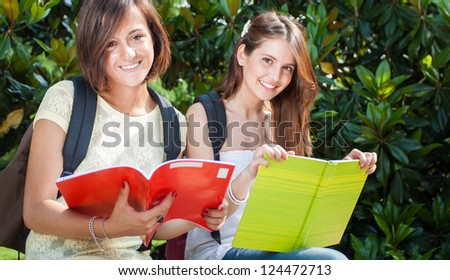 Portrait of two students reading in a park - stock photo