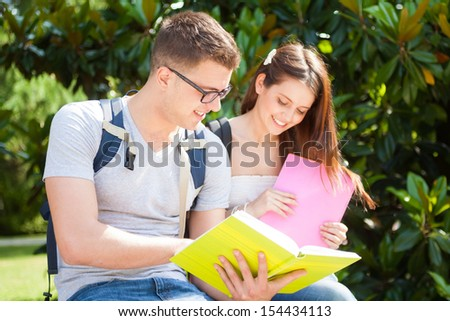 Portrait of two students talking in a park - stock photo